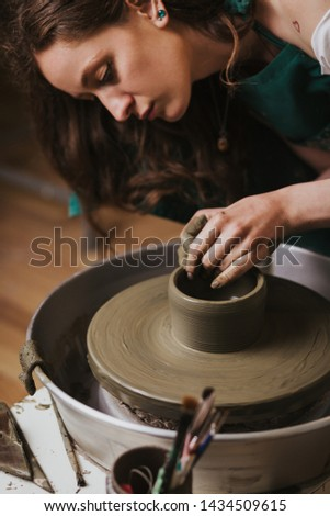 Artisan woman working on pottery wheel and making a pot.