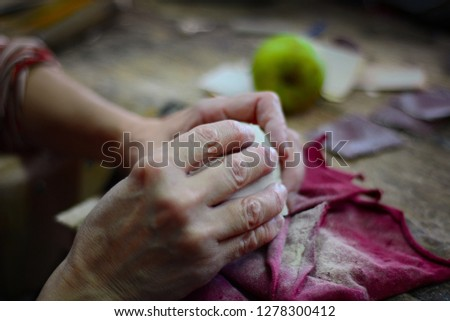 Artisan woodcarver works with sandpaper to polish a wooden ball - replica of an apple. Soft focus photo of woodcarver's hands, pieces of sandpaper and a green apple on the top of a bench.
