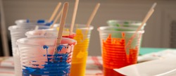 Artist acrylic colours in plastic cups in art studio, preparing for painting, panorama