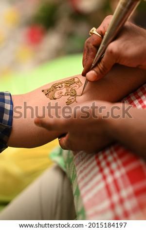 Artist applying henna or tattoo on hands. henna drawing mehendi Stock photo ©