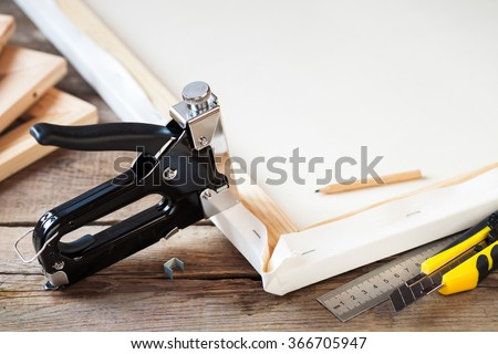 Artist canvas, canvas stretcher and staple gun on table #366705947