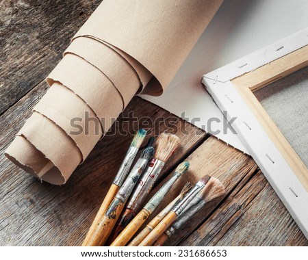 Artist canvas in roll, canvas stretcher and paintbrushes on old table
