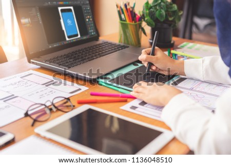 Artist creative designer hands sketching of screens for mobile responsive website development with UI/UX. Developing wireframe sketch layout design mockup on smartphone screen. #1136048510