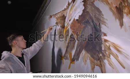 Artist designer draws an eagle on the wall. Craftsman decorator paints picture with acrylic oil color. Painter painter dressed in paint coat. Indoor. Stock photo ©