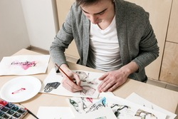 Artist doing design of fashion footwear model. Young man makes fashion sketch on his workplace with artistic tools around