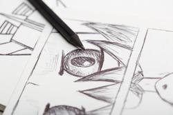 Artist drawing an anime comic book in a studio.