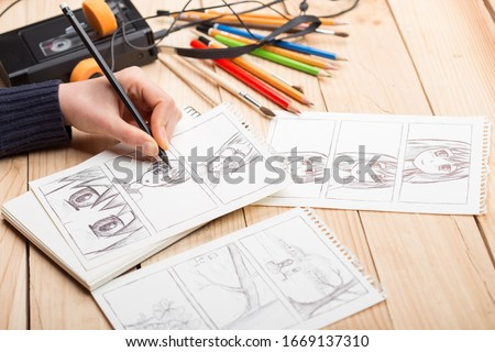 Photo of  Artist drawing an anime comic book in a studio. Wooden desk, natural light. Creativity and inspiration concept.