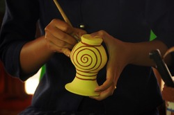 Artist  drawing paint pattern on pottery, making of handcraft pottery at Ban Chiang, Udon Thani, Thailand