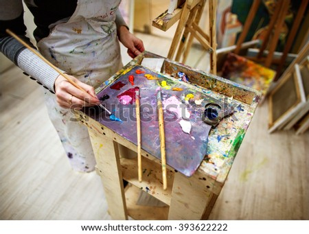 artist draws a picture in an apron, easel and paint palette
