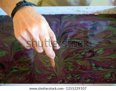 Artist Ebru, the art of painting on water creates a drawing. The process of creating a picture in the technique of Ebru. Marmaris. Turkey