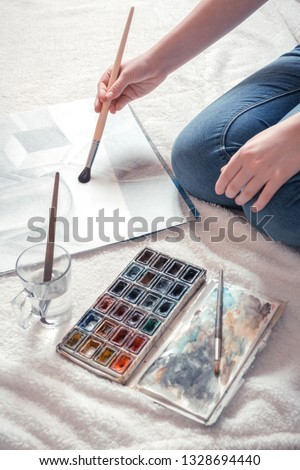 Artist Girl paints on canvas painting on an easel. Hobbies and hobbies relax modern youth generation z, light background