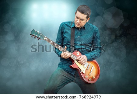 Artist Guitarist hands play on electricity guitar under light, Practicing in playing . Song entertainment and music instrument. #768924979
