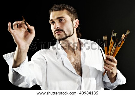 artist in a white shirt on a black background with a brush. contrast shot