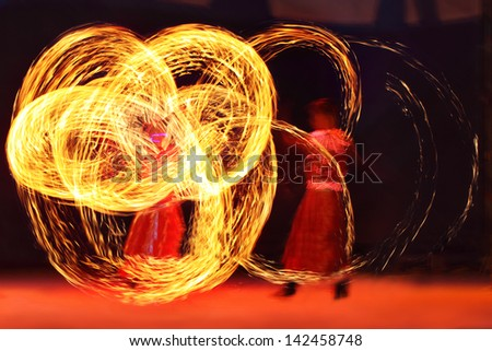Artist juggling with two burning poi's at fire performance. Long exposure causing painting with light