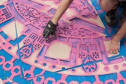 Artist make street art on the sidewalk using spraypaint and  stencils