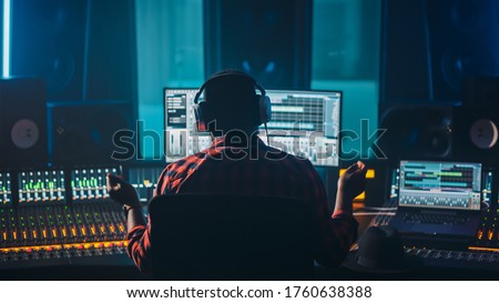 Artist, Musician, Audio Engineer, Producer in Music Record Studio, Uses Control Desk with Computer Screen showing Software UI with Song Playing. Success with Raised Hands, Dances. Back View. Foto d'archivio ©
