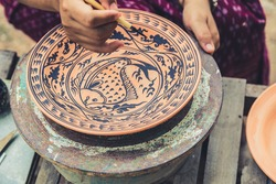Artist paint drawing fish in Sukhothai traditional style pattern with black color in earthenware, making of handcraft pottery in Sukhothai, Thailand.