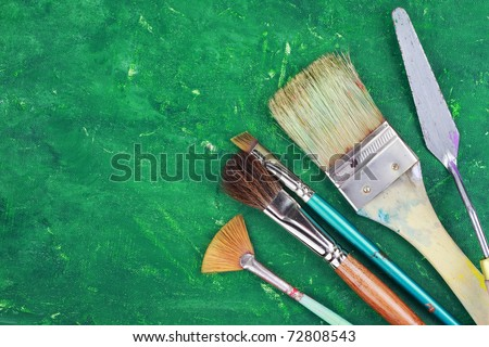 Artist paintbrushes and palette knife against an abstract grunge painting.