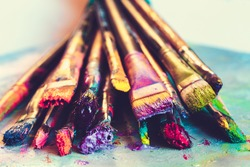 Artist paintbrushes with paint closeup on artistic canvas. Retro toned. Selective focus.
