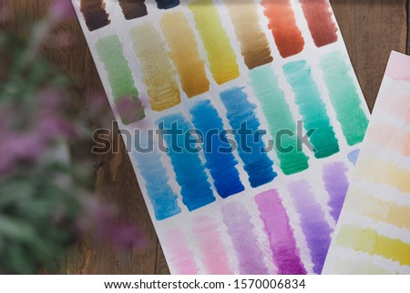 Artist painted watercolour swatch palette on wooden workstation background - Flat lay overhead view of various colour swatches used for color matching - spectrum, creative and artistic concepts