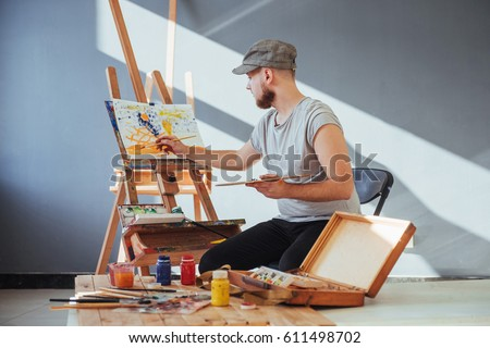artist painting a picture in a studio. #611498702
