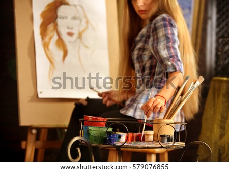 Artist painting on easel in studio. Girl paints portrait of woman with brush. Female painter seen from behind. Indoor home interior for handmade crafts. #579076855
