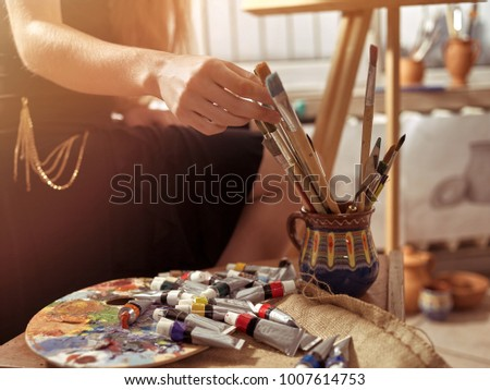 Artist painting on easel in studio. Girl paints with brush in morning sunlight dawn light toning. Indoor home interior for handmade crafts with window background. Selection of materials for drawing.
