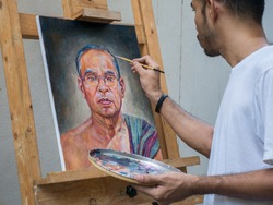 Artist painting portrait of asian man,oil color on canvas,which place on easel