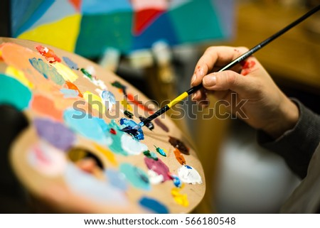 artist painting with acrylic colors and mixing tones on the pallet. blur background abstract photo #566180548