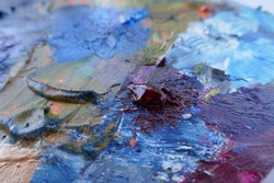 Artist, palette with paints, brushes and a palette knife on a white background.