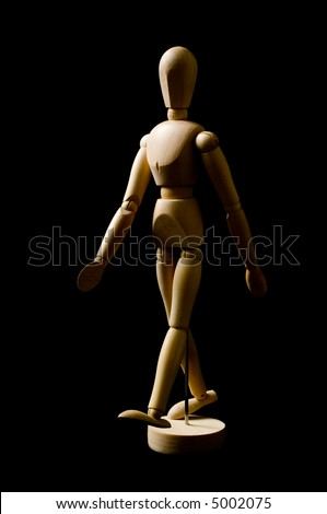 Artist person posing doll in walking gesture on black background, lit from the side to provide shape - stock photo