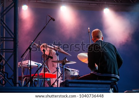 Artist playing on keyboard synthesizer piano keys, man playing drums on stage during music festival in summer. Band performing their songs. Live concert of electronic music at night. Colorful lights #1040736448
