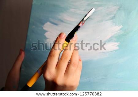 Artist�¢??s hand holding a paintbrush