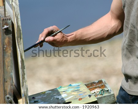 Artist's hand with a brush painting a study