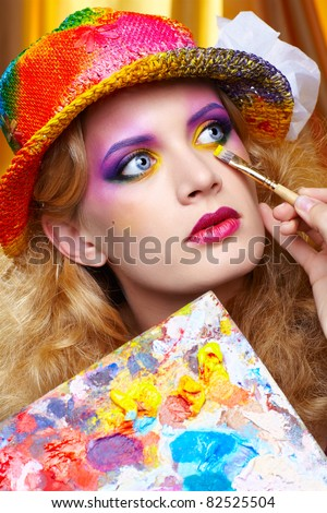 artist's hand with paintbrush painting beautiful girl's colorful eye shadow make up using palette