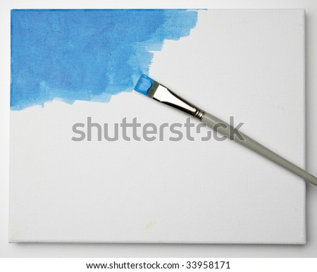Artist uses brush to paint a canvas blue