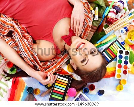 Artist woman lying on paint palette.