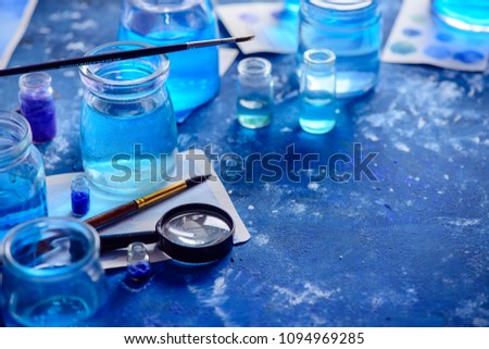 Artist workplace with watercolor sketches in shades of blue. Monochromatic painting with glass jars, paint and brushes. Drawing sea concept with copy space. #1094969285