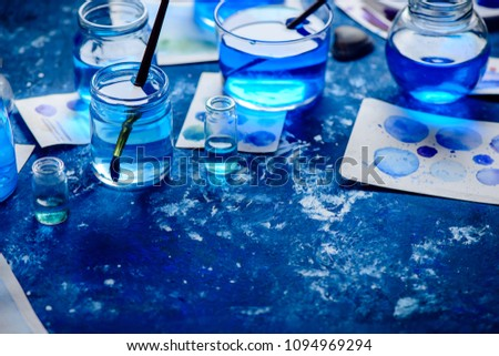 Artist workplace with watercolor sketches in shades of blue. Monochromatic painting with glass jars, paint and brushes. Drawing sea concept with copy space. #1094969294