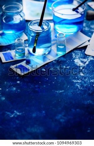 Artist workplace with watercolor sketches in shades of blue. Monochromatic painting with glass jars, paint and brushes. Drawing sea concept with copy space. #1094969303