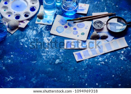 Artist workplace with watercolor sketches in shades of blue. Monochromatic painting with glass jars, paint and brushes. Drawing sea concept with copy space. #1094969318