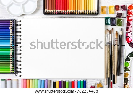 Artist workspace on white wooden background. Top view. Mock up.
