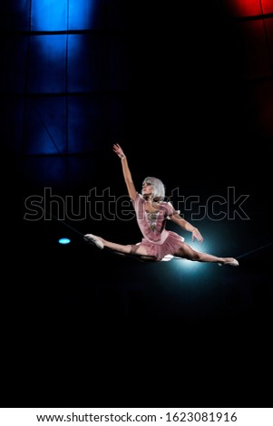 artistic aerial acrobat doing splits while performing in circus