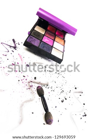 Artistic arrangement of colourful eye makeup in a box with an applicator and scattered remnants and squiggles of powdered cosmetic in the foreground on white