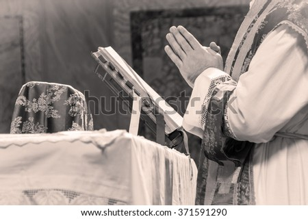 Artistic black and white dark vintage edit of a priest saying the extraordinary form, traditional latin tridentine rite Catholic mass. A detail.