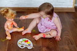 Artistic child. Colorful childhood, creative baby girl. Early children education. Creativity concept. Little baby painting on doll. Baby child draws with colored paints hands, dirty feet and fingers