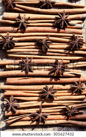 Artistic closeup of cinnamon and star anise seeds on a wooden background. Sunny still life photo. Top view
