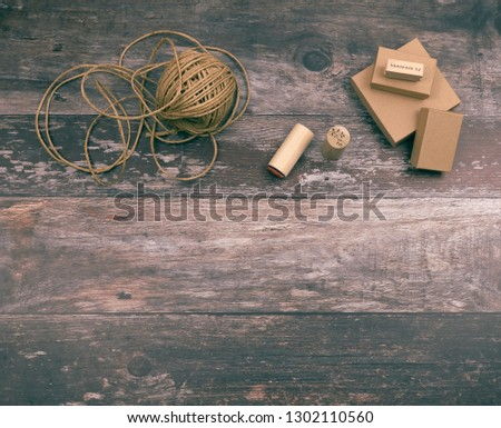 Artistic crafting supplies and art tools of hemp yarn, natural cardboard boxes and stamps for creative homemade gift wrapping and handmade crafts, on wood background with copyspace