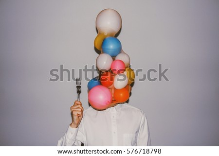 Artistic creative photography. Man wearing white shirt, delicate balloons and holding a sharp fork.