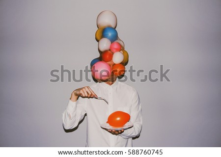 Artistic creative photography. Man wearing white shirt, delicate balloons and holding a sharp fork and a plate with balloon.